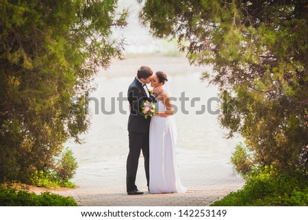 bride and groom outdoors park under trees arc - stock photo