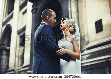 Bride and groom posing and hugging near old baroque church - stock photo