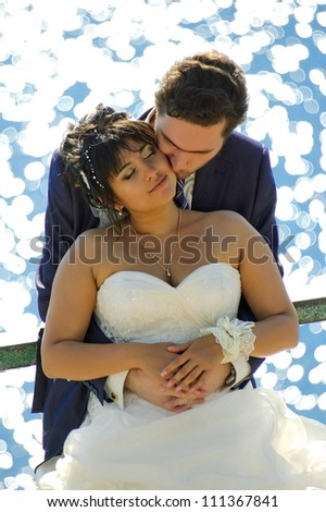 Bride and groom posing on a background glare on the water, backlit - stock photo