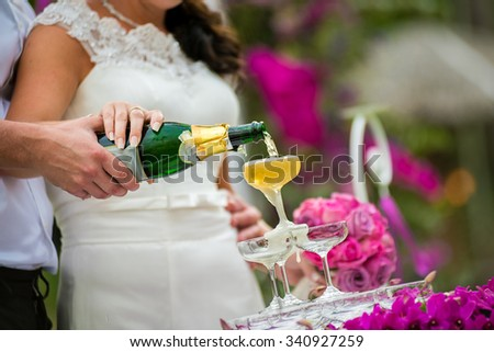 Bride and groom pouring champagne into the glass - stock photo