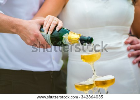 Bride and groom pouring champagne into the glass