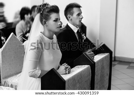 bride and groom preparing for communion on knees at wedding ceremony in church - stock photo
