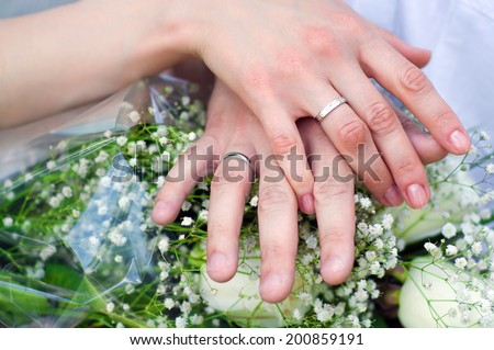Bride and groom put their hands together near the wedding bouquet and show the rings of silver color