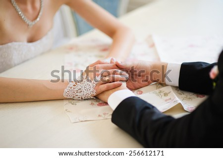 Bride and groom's hands at wedding ceremony - stock photo