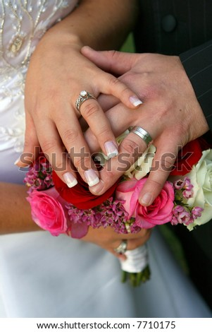 bride and groom's hands on bouquet - stock photo