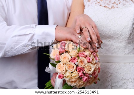 Bride and Groom's hands. Wedding bouquet.