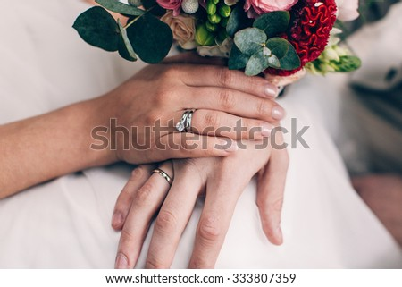 Bride and groom's hands with wedding and engagement rings - stock photo