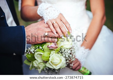 Bride and groom's hands with wedding rings near wedding bouquet - stock photo