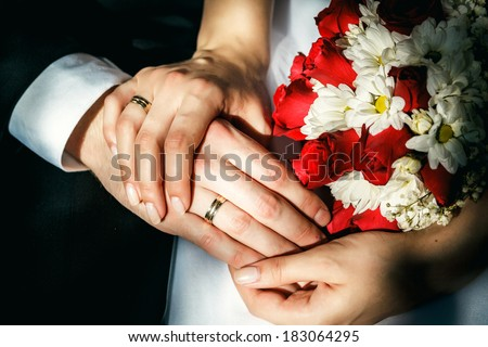 Bride and groom's hands with wedding rings, wedding bouquet. - stock photo