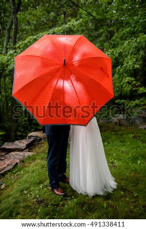 Bride and Groom share a kiss behind umbrella