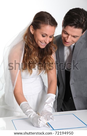 Bride and groom signing marriage contract - stock photo