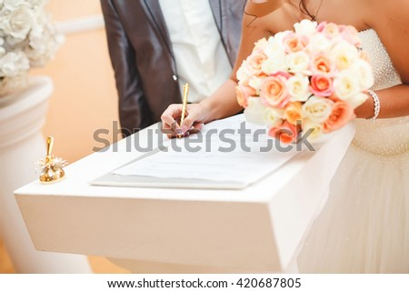 Bride and groom signing marriage wedding certificate at registry - stock photo