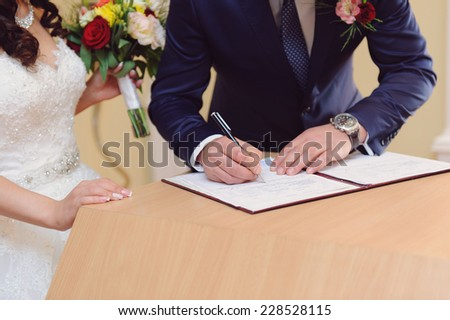 bride and groom signing wedding contract - stock photo