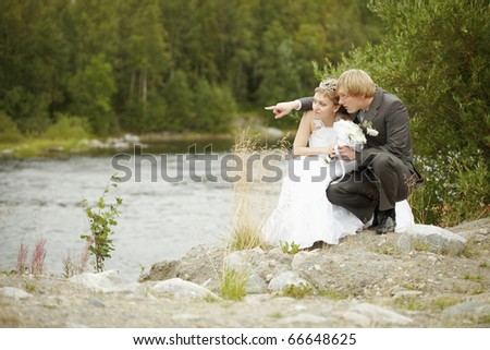 Bride and groom sit on riverbank - stock photo