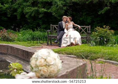 Bride and groom sitting in the park with blurred bouquet downstage - stock photo