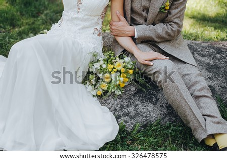 bride and groom sitting on a rock in the middle of green fields next to a bouquet of white and yellow flowers with green