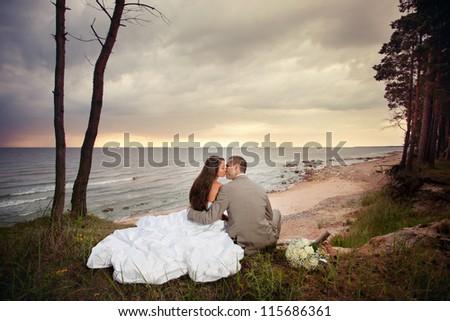 Bride and groom sitting on the beach and kissing. - stock photo