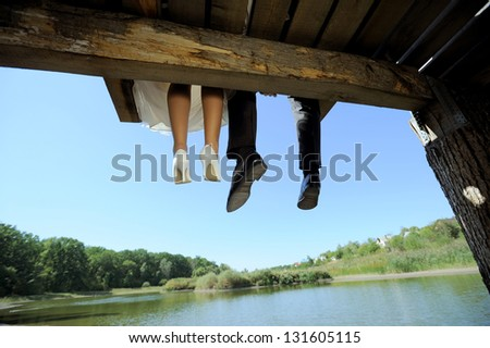 bride and groom sitting on wooden bridge in park - stock photo