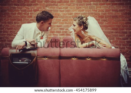 Bride and groom smile to each other sitting on the different couches
