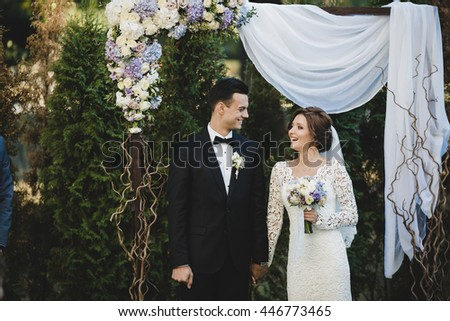 Bride and groom smile to each other standing under the beautiful wedding altar