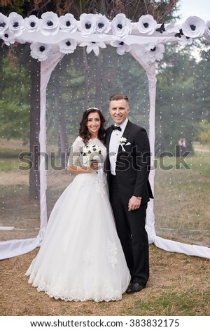 bride and groom stand near arch at wedding ceremony