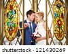 Bride and groom stand near beautiful colorful stained glass windows - stock photo
