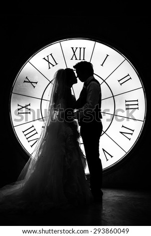 bride and groom stand on background big clock.