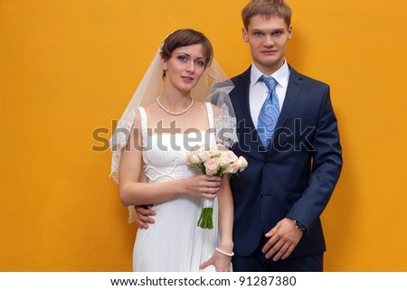 Bride and groom standing against yellow wall - stock photo