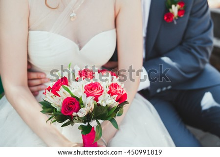 Bride and groom standing and hugging the bride holds a beautiful wedding bouquet - stock photo
