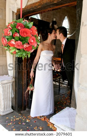 Bride and groom standing in chapel doorway next to hanging flowers - stock photo