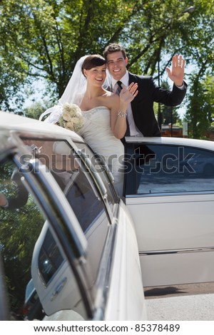 Bride and groom standing in Limo waving - stock photo