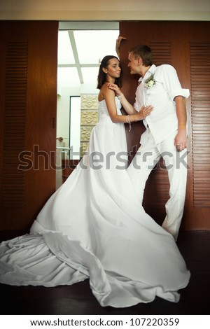 bride and groom standing near the wood door in the room - stock photo