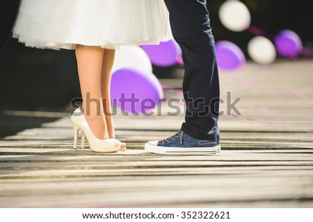 bride and groom standing on bridge at sunny day - stock photo
