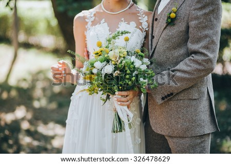 bride and groom standing on green grass and holding a bouquet of white and yellow flowers with green - stock photo