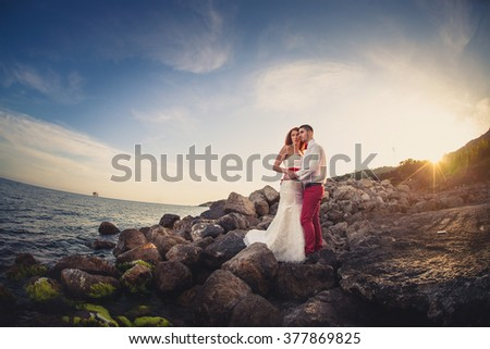 Bride and groom standing on the edge of the rocks on the background of the sea. Sunset