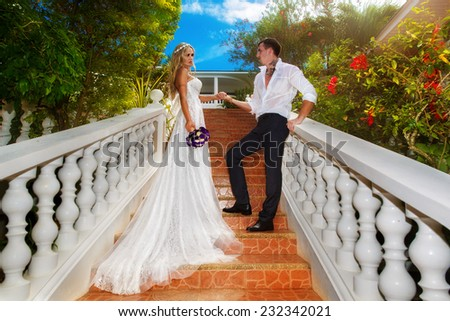 Bride and groom standing on the stairs in the hotel on a tropical island. Wedding and honeymoon. - stock photo