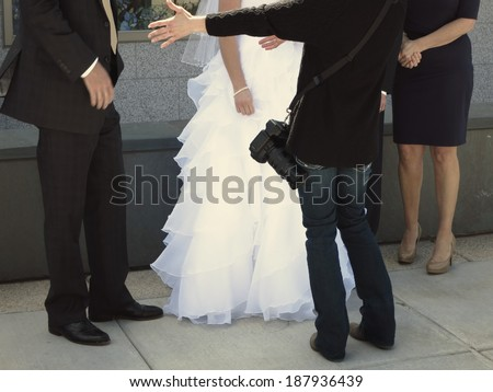 Bride and groom standing together with flowers on wedding day photographer directing for photographs - stock photo