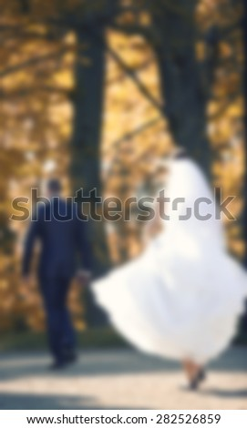 bride and groom standing under big tree on green grass,abstract blurred wedding background,love and marriage background