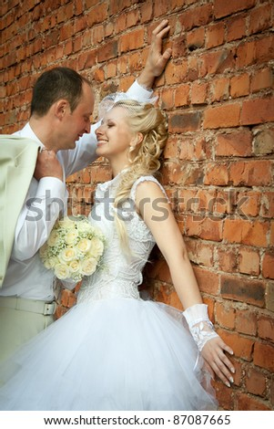 Bride and groom staying near the wall of brick - stock photo