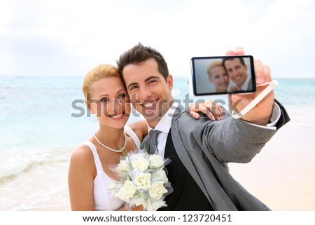 Bride and groom taking picture of themselves - stock photo