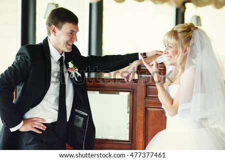 Bride and groom talk while laughing in a restaurant