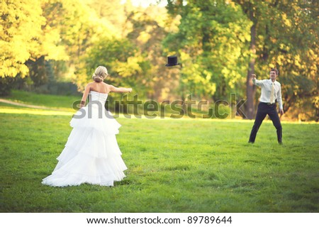 Bride and Groom throwing a hat in a park