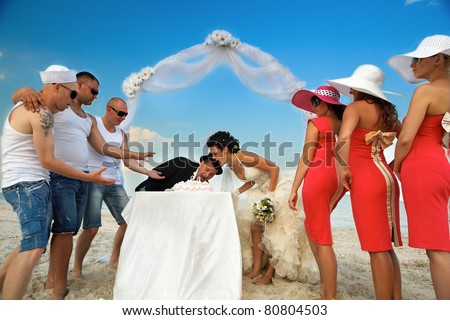 Bride and Groom Under Archway on Beach trying to take a bite of wedding cake. - stock photo