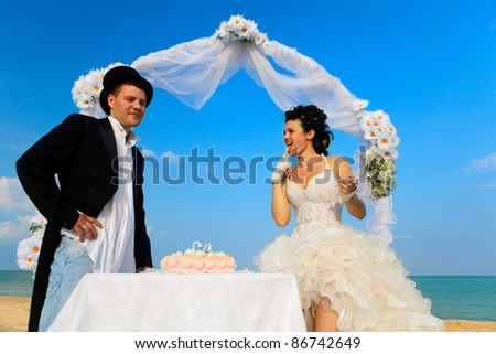Bride and Groom Under Archway on Beach with wedding cake. Bride putting bit of cake on groom's nose - stock photo