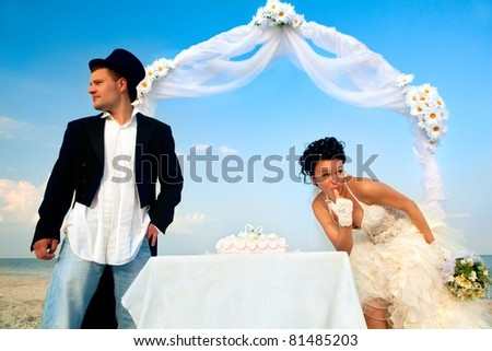 Bride and Groom Under Archway on Beach with wedding cake. Bride trying bit of cake and looking around that nobody see - stock photo
