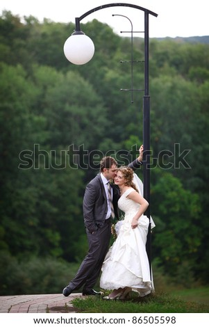 Bride and groom under lantern in summer park - stock photo