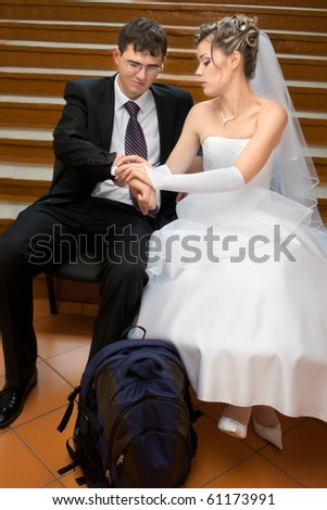 Bride and groom waiting for departure with a backpack on floor