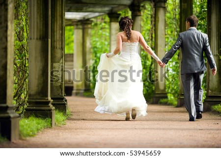 Bride and groom walking away in summer park outdoors - stock photo
