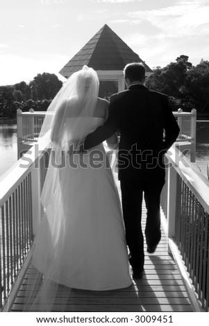 Bride and groom walking down a gazebo on a lake - stock photo