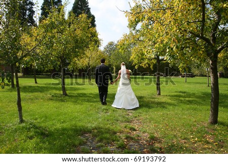 Bride and groom walking in a country orchard.